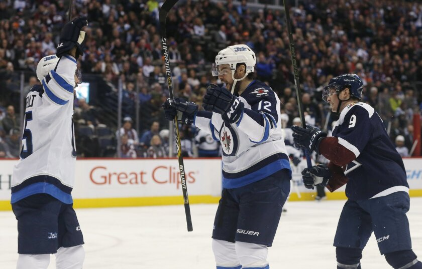 Winnipeg Jets center Mathieu Perreault, left, celebrates with right wing Drew Stafford, center, after Stafford's goal, as Colorado Avalanche center Matt Duchene skates past during the second period of an NHL hockey game Saturday, Feb. 6, 2016, in Denver. (AP Photo/David Zalubowski)