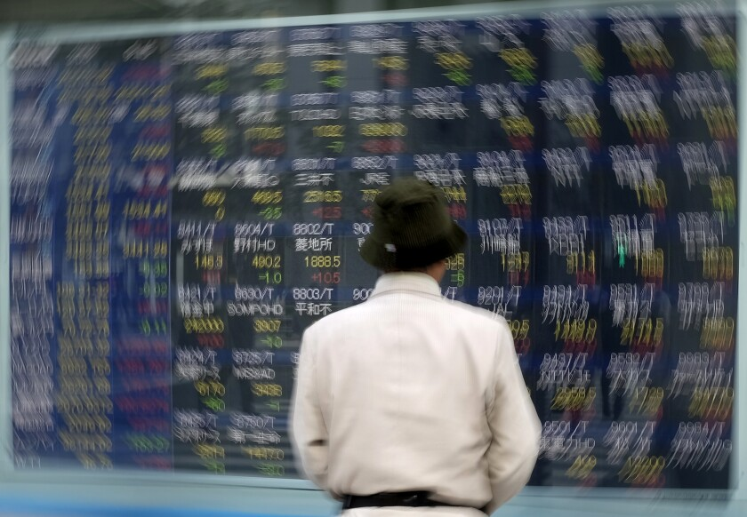 A pedestrian pauses in front of an electronic board at the Tokyo Stock Exchange.