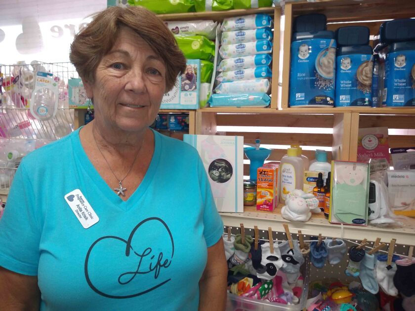 Anita Krisik, Ramona Pregnancy Care Clinic's executive director, displays baby supplies in the clinic's Mommy and Me Market.