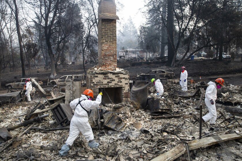 in November 2018, search and rescue teams inspect the grounds of a house burned by the Camp fire in Paradise, Calif.