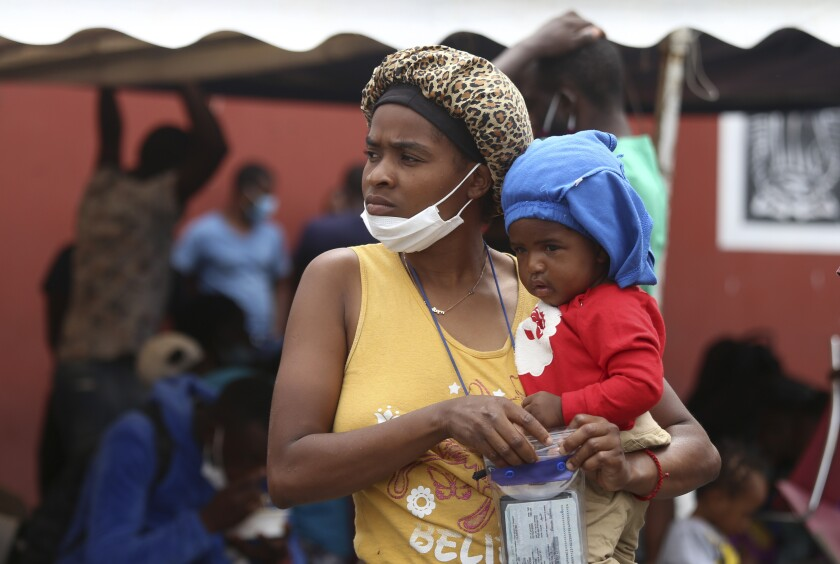 A Haitian migrant woman holds a child in her arms at the Padre Infante shelter, in Monterrey, Mexico, Wednesday, Sept. 22, 2021. (AP Photo/Roberto Martinez)
