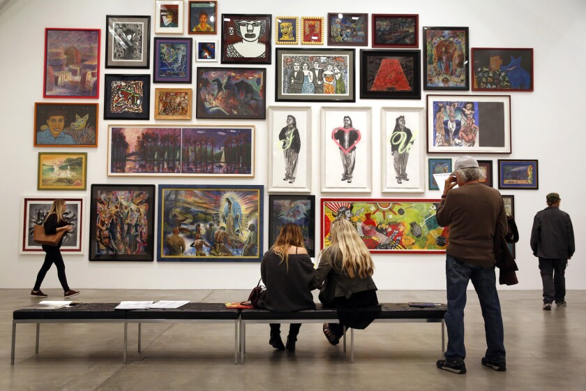 """Attendees peruse art from the collection of Cheech Marin at the Museum of Contemporary Art San Diego's monthly """"Downtown at Sundown"""" event, where the downtown museum is free and open until 8 p.m. on the third Thursday of every month."""
