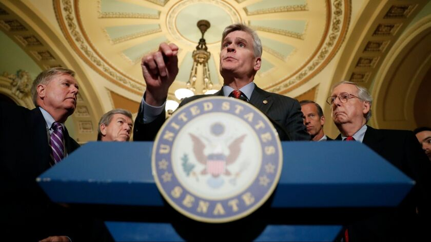 Sen. Bill Cassidy, R-La., center, speaks to the media, accompanied by Sen. Lindsey Graham, R-S.C., left, and Senate Majority Leader Mitch McConnell on Capitol Hill in Washington on Sept. 19.
