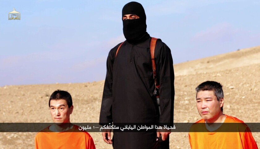 A video purportedly released by Islamic State on Jan. 20 shows Japanese hostages Kenji Goto, left, and Haruna Yukawa with a militant at an undisclosed location.