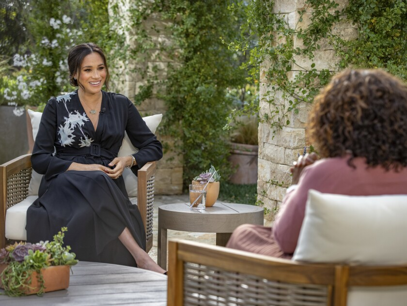 """This image provided by Harpo Productions shows Meghan, Duchess of Sussex, left, speaking with Oprah Winfrey during an interview. """"Oprah with Meghan and Harry: A CBS Primetime Special"""" airs March 7 as a two-hour exclusive primetime special on the CBS Television Network. (Joe Pugliese/Harpo Productions via AP)"""