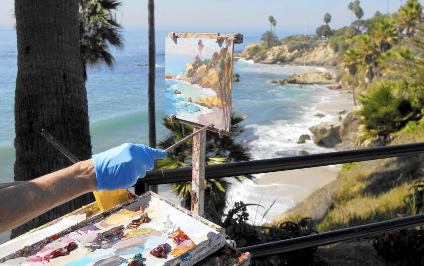 The steady hand of artist Kathleen Robison paints the beach at Rockpile in this file photo. The Laguna Beach Plein Air Painting Invitational will be held Oct. 8-16.