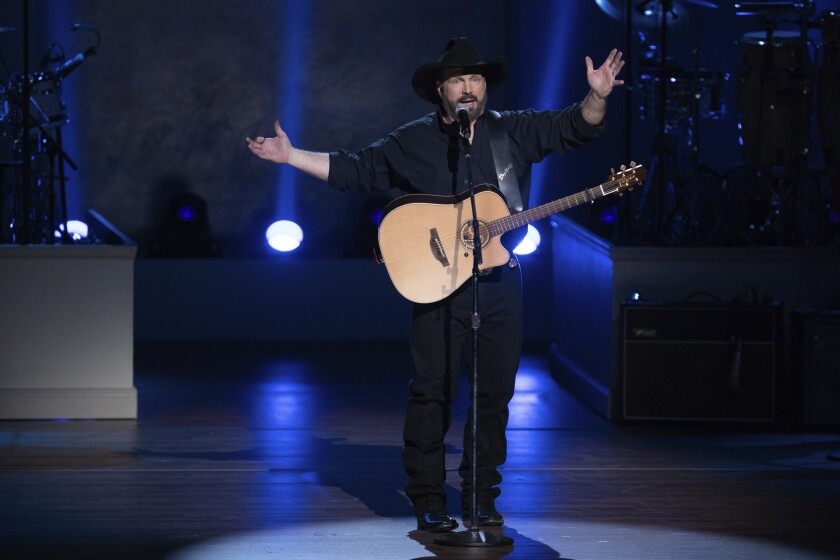 FILE - In this March 4, 2020, file photo, country star Garth Brooks performs on stage during the 2020 Gershwin Prize Honoree's Tribute Concert at the DAR Constitution Hall in Washington. Brooks said he will be reassessing whether to continue his stadium tour because of the rising number of COVID-19 cases. In a statement issued on Tuesday, Aug. 3, 2021, Brooks said he is still scheduled to play the next two shows scheduled in Kansas City and Lincoln, Nebraska, but will not put tickets on sale for the next planned stop, Seattle in September. (Photo by Brent N. Clarke/Invision/AP, File)