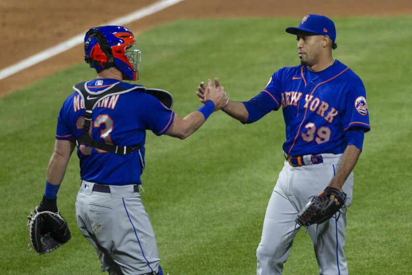 New York Mets closing pitcher Edwin Diaz (39) is congratulated by catcher James McCann (33) after their team defeated the Philadelphia Phillies in a baseball game, Saturday, May 1, 2021, in Philadelphia. (AP Photo/Laurence Kesterson)