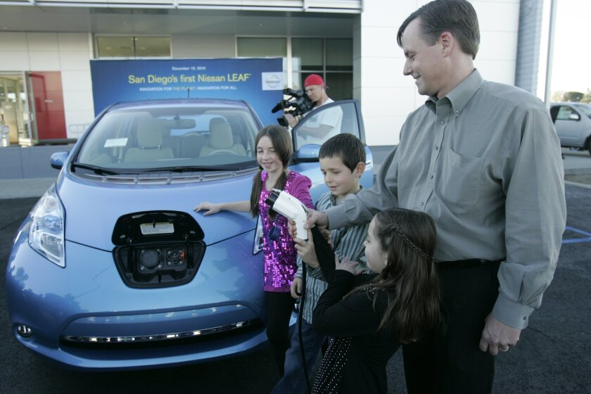 Tom Franklin and his children, Audrey, William and Olivia, test out the charging plug for their new Nissan Leaf, the second model ever delivered to a customer.