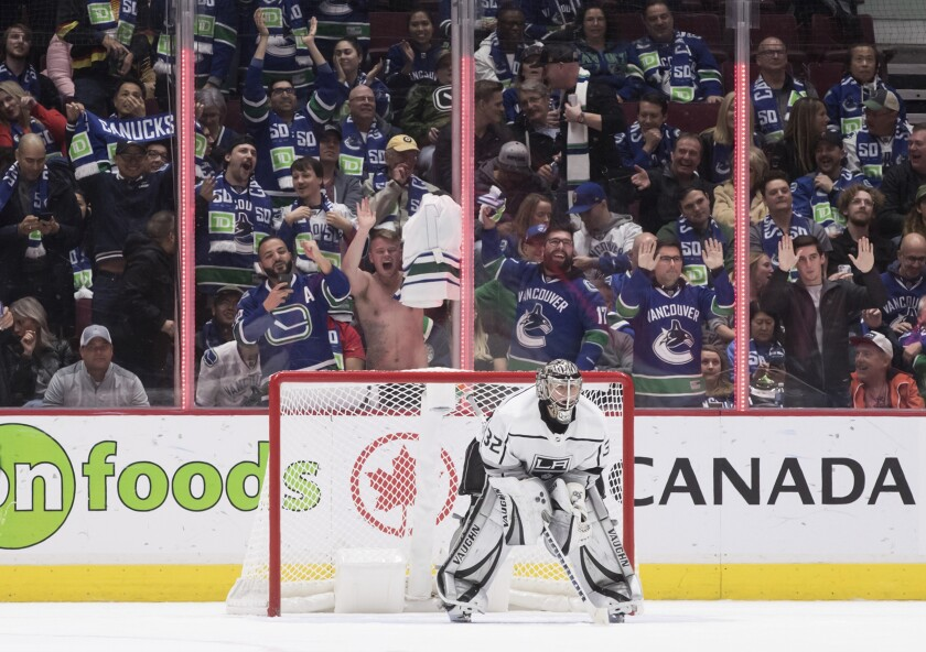 Vancouver fans celebrate behind Kings goalie Jonathan Quick after the Canucks scored their eighth goal of the night.