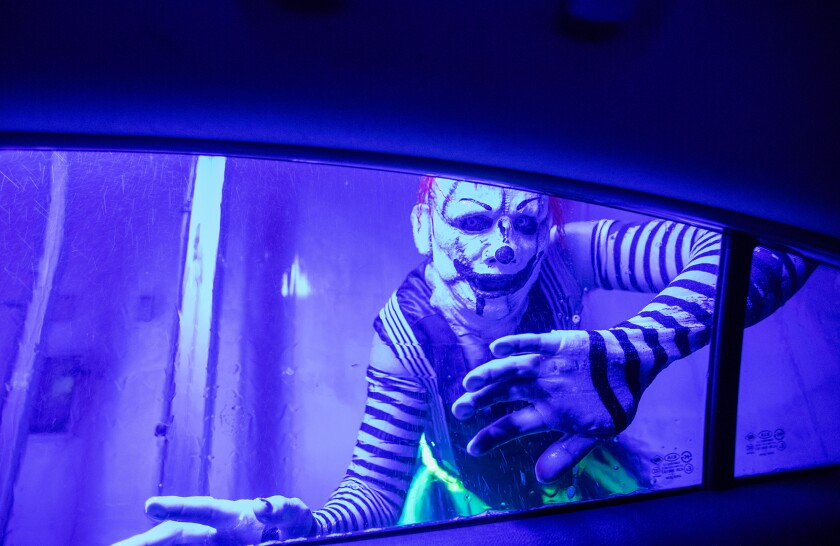 A ghoul peeks in the window at Russell Fischer Xpress Car Wash in Huntington Beach on Thursday.