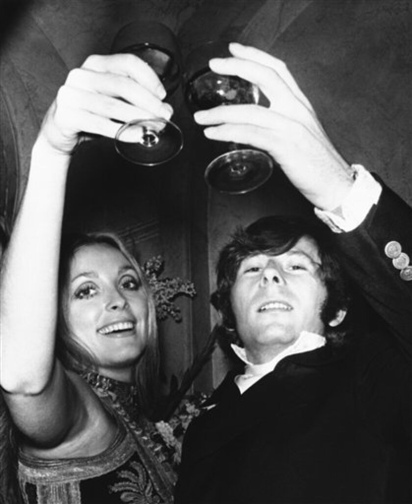 "FILE - In this Feb. 18, 1969 file photo, Roman Polanski is shown with his wife, the actress Sharon Tate, toasting the opening of ""Rosemary's Baby"" in London. A topless photo of Polanski and Tate, taken just months before her death has sold at a New York City auction for $11,250. Christie's says it was sold Monday Dec. 7, 2009 to an unidentified private buyer. (AP Photo)"