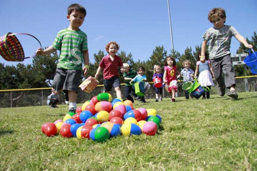 Children run to the eggs at an Eggstravaganza festival at Poinsettia Community Park in Carlsbad.