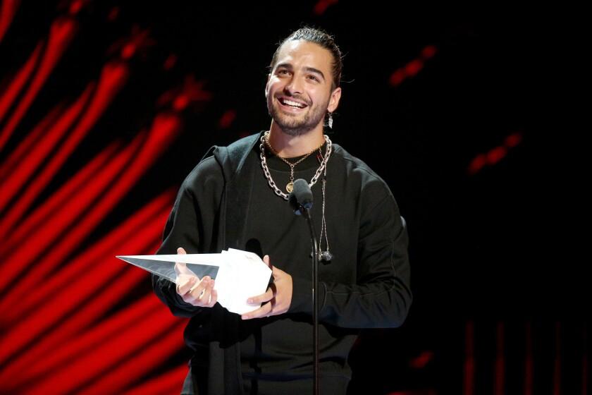 Maluma acepta el premio a la Evolución en medio de la ceremonia de premiación.