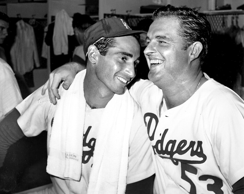 Baseball pitchers Sandy Koufax, left, and Don Drysdale (53) share a laugh in the dressing room at Dodger Stadium after winning the National League pennant on Oct. 2, 1965.