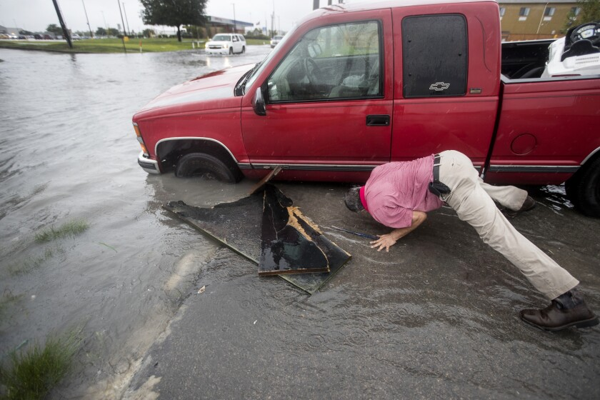Felipe Morales works on getting his truck out of a ditch filled with high water on Sept. 17 in Houston. Another driver helped pull him out.