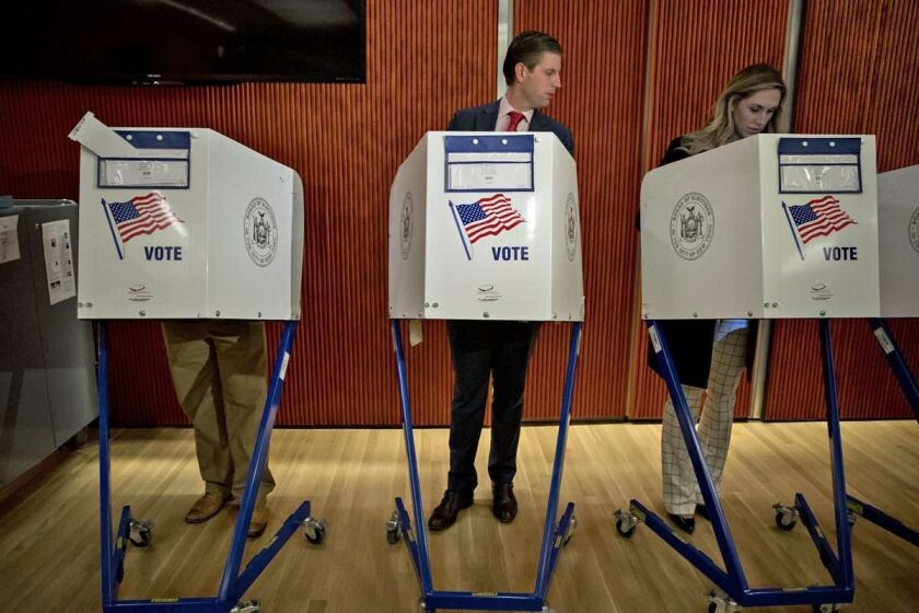 The President's son Eric Trump looks at his wife's voting booth at the 53rd Street Library in New York.
