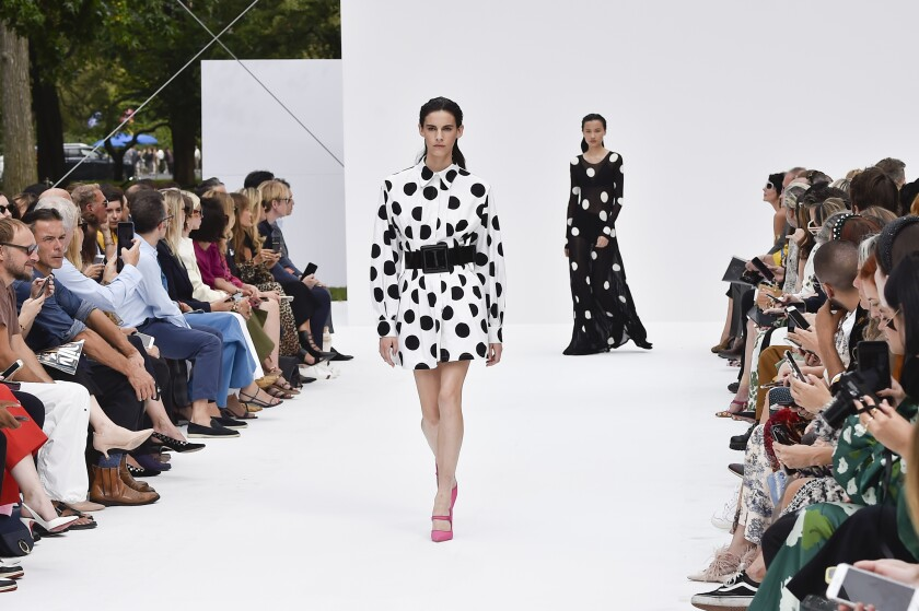 Two models walk the runway in polka-dotted looks from Carolina Herrera: one in a short white dress with black spots; the other, a long black dress with white spots