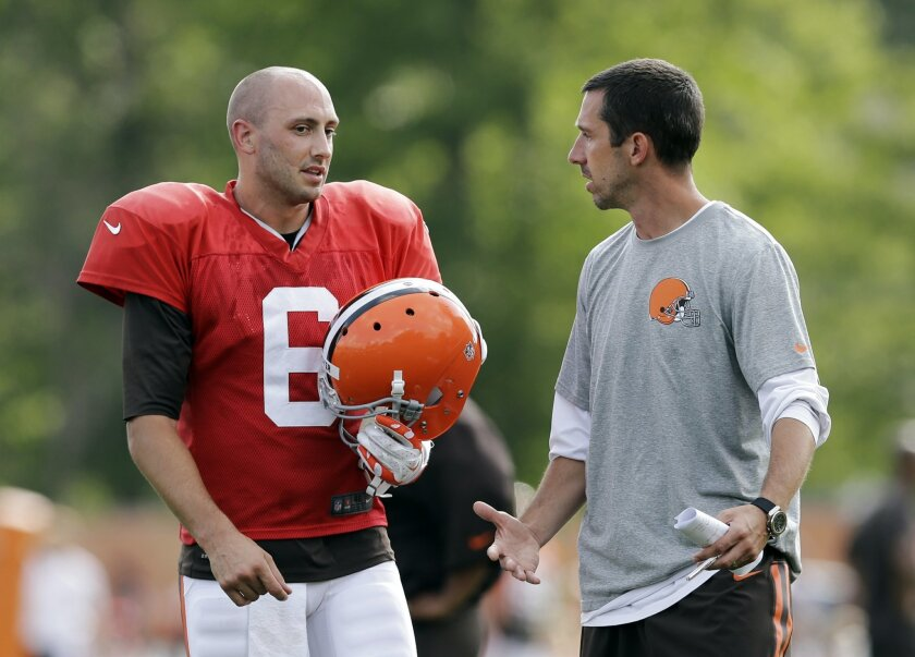 Cleveland Browns quarterback Brian Hoyer (6) talks with offensive coordinator Kyle Shanahan during practice at NFL football training camp in Berea, Ohio Wednesday, Aug. 6, 2014. Coach Mike Pettine is expected to name his starting quarterback for Saturday night's exhibition opener in Detroit. Hoyer is listed first on the team's depth chart, but rookie Johnny Manziel may be gaining on him. (AP Photo/Mark Duncan)