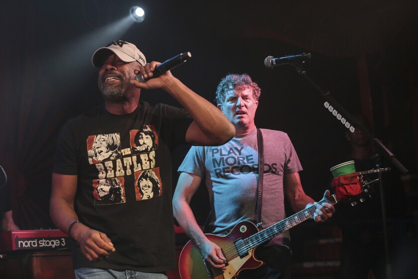 "Hootie & the Blowfish singer Darius Rucker, in a black Beatles' ""Let It Be"" album cover T-shirt, and guitarist Mark Bryan, in a gray T-shirt that says ""Play More Records."""