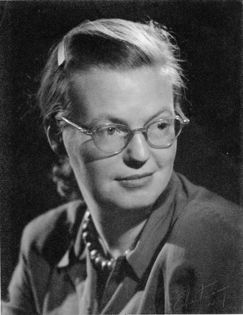 A black and white portrait of author Shirley Jackson, wearing glasses and pearls with a button down blouse.