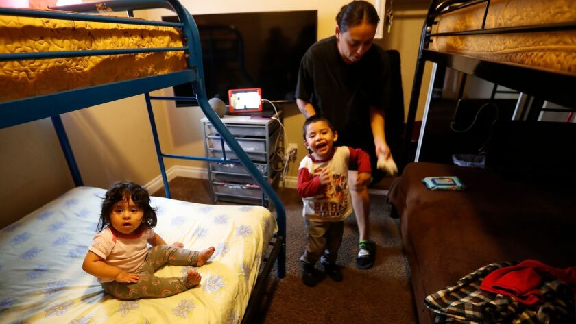 Annabel Vasquez, 35, her son Andrew Flores, 3, and daughter Aliah Flores, 1, relax in a South Los Angeles home. The five-bedroom house is part of the Shelter Crisis Housing program, which takes Hopics clients.