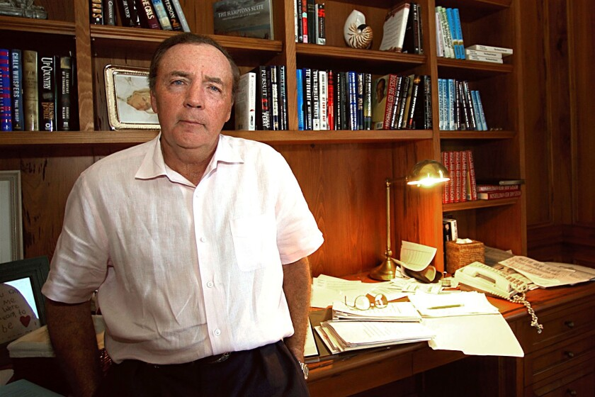 James Patterson in front of a desk and bookshelves