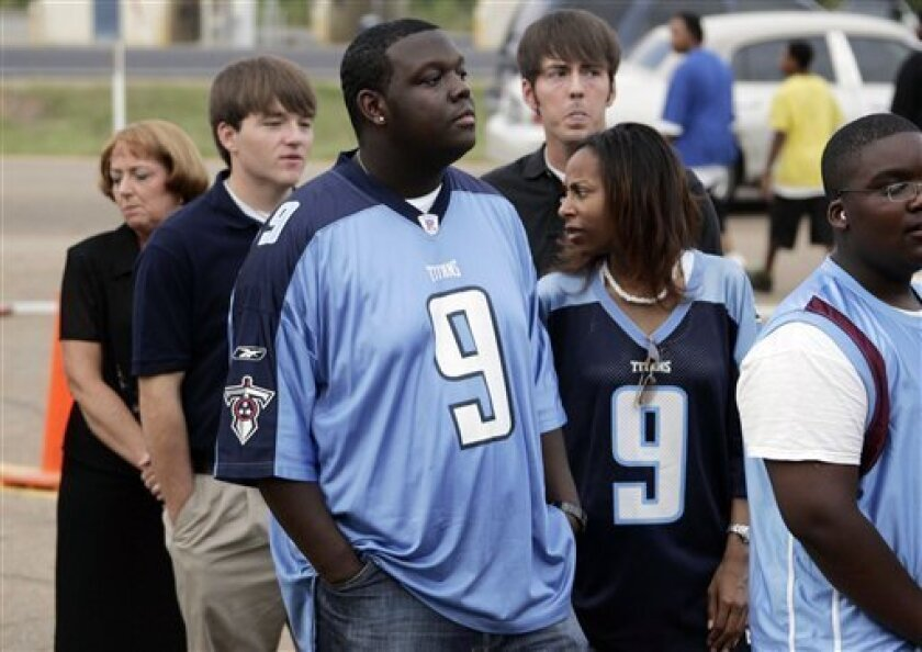 Kenny Stewart and Shameca Collins of Natchez, wear McNair's Tennessee Titans home and travel jerseys as they wait in line for about 90 minutes to pay their respects to the late former NFL star at Reeves Funeral Home in Mount Olive, Miss., Friday, July 10, 2009. About 1,000 people battled warm temperatures and high humidity for the opportunity to say goodbye to the athlete. (AP Photo/Rogelio V. Solis)