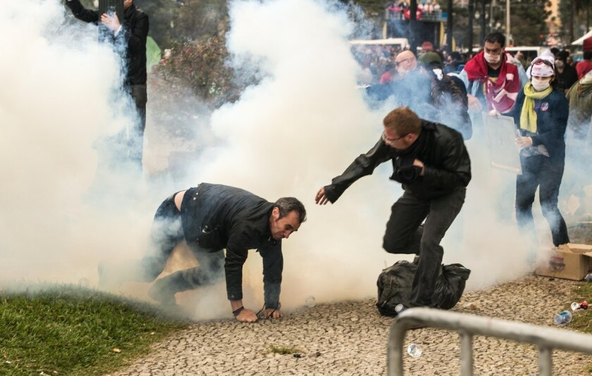 Teachers and police clash in downtown Curitiba, Brazil, on April 29, 2015 during protests by teachers seeking better wages and working conditions.