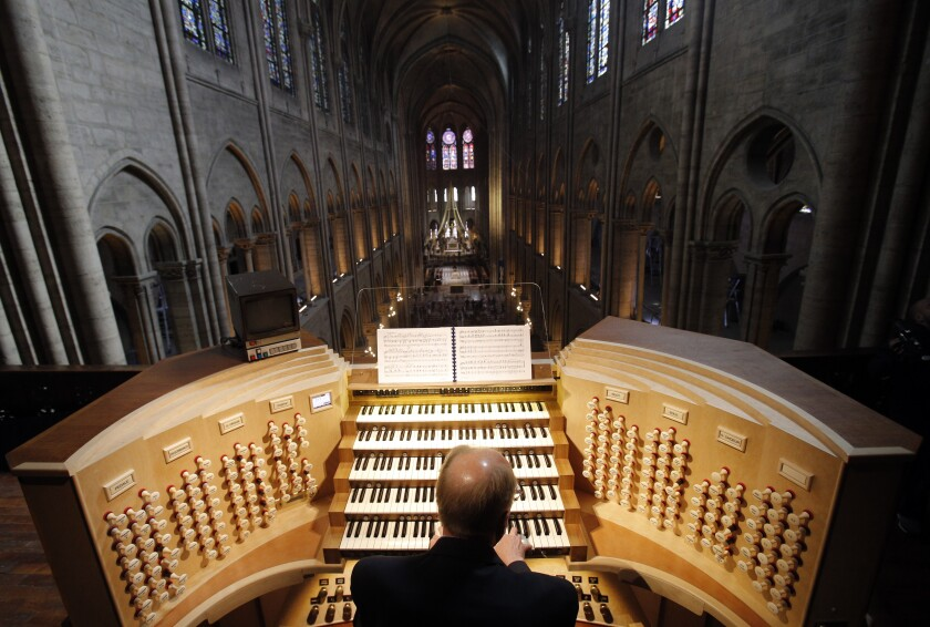 FILE - In this Thursday, May 2, 2013 file photo, Philippe Lefebvre, 64, plays the organ at Notre Dame cathedral in Paris. Pipe by precious pipe, the organ that once thundered through fire-ravaged Notre Dame Cathedral is being taken apart. The mammoth task of dismantling, cleaning and re-assembling France's largest musical instrument started Monday Aug.3, 2020 and is expected to last nearly four years. (AP Photo/Christophe Ena, file)
