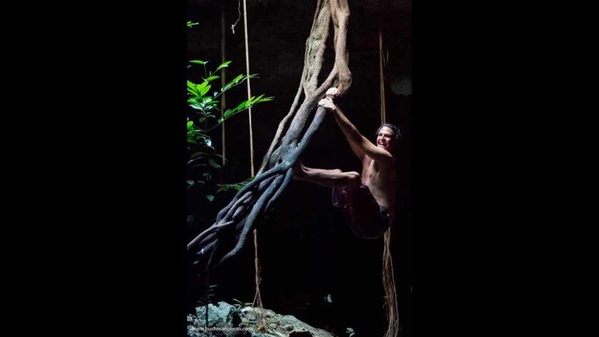 A trip to Mexico's Yucatan peninsula offers a photography tour that seeks to let visitors get a glimpse of permaculture, a concept that embraces care for the earth, care for people and fair share. Here Vincent Crampton of Gotha, Fla., hangs from a vine in a cenote.