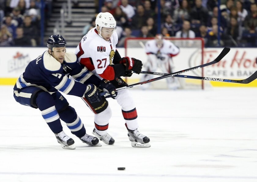 Ottawa Senators' Curtis Lazar, right, carries the puck up the ice as Columbus Blue Jackets' Gregory Campbell defends during the first period of an NHL hockey game Saturday, Feb. 13, 2016, in Columbus, Ohio. (AP Photo/Jay LaPrete)
