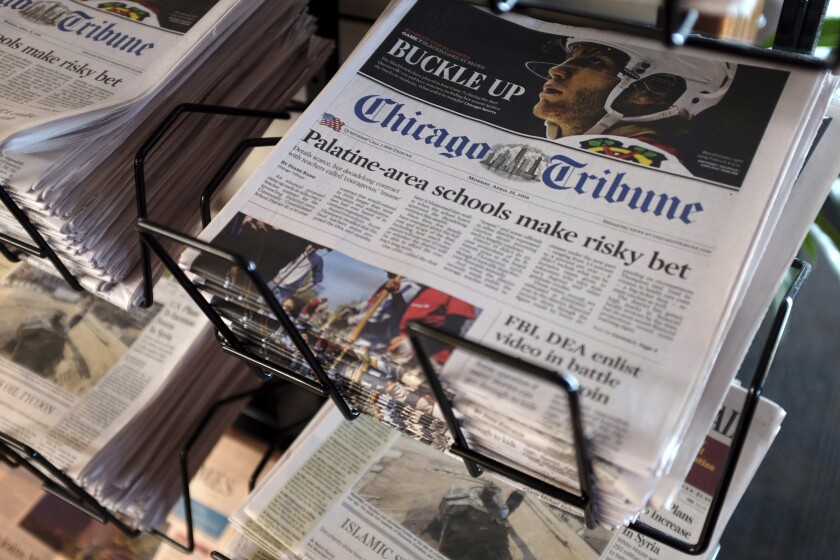 Copies of Chicago Tribune newspapers sit in a rack.