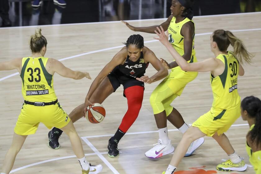 Aces forward A'ja Wilson drives against Storm defenders (from left) Sami Whitcomb, Natasha Howard and Breanna Stewart.