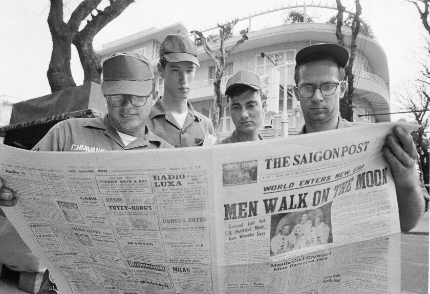 American servicemen pause on a downtown Saigon, Vietnam, street on July 21, 1969, to read a local newspaper account of the Apollo 11 lunar landing.