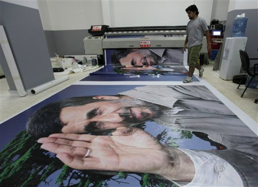 A Lebanese worker, works next to a machine printing a huge poster of Iranian President Mahmoud Ahmadinejad, at a print shop in the southern suburb of Beirut, Lebanon, on Wednesday Oct. 6, 2010, ahead of the Iranian leader's three-day visit to Lebanon that begins on Oct. 13. The U.S. has raised concerns about Iranian President Mahmoud Ahmadinejad's visit to Lebanon next week. (AP Photo/Hussein Malla)