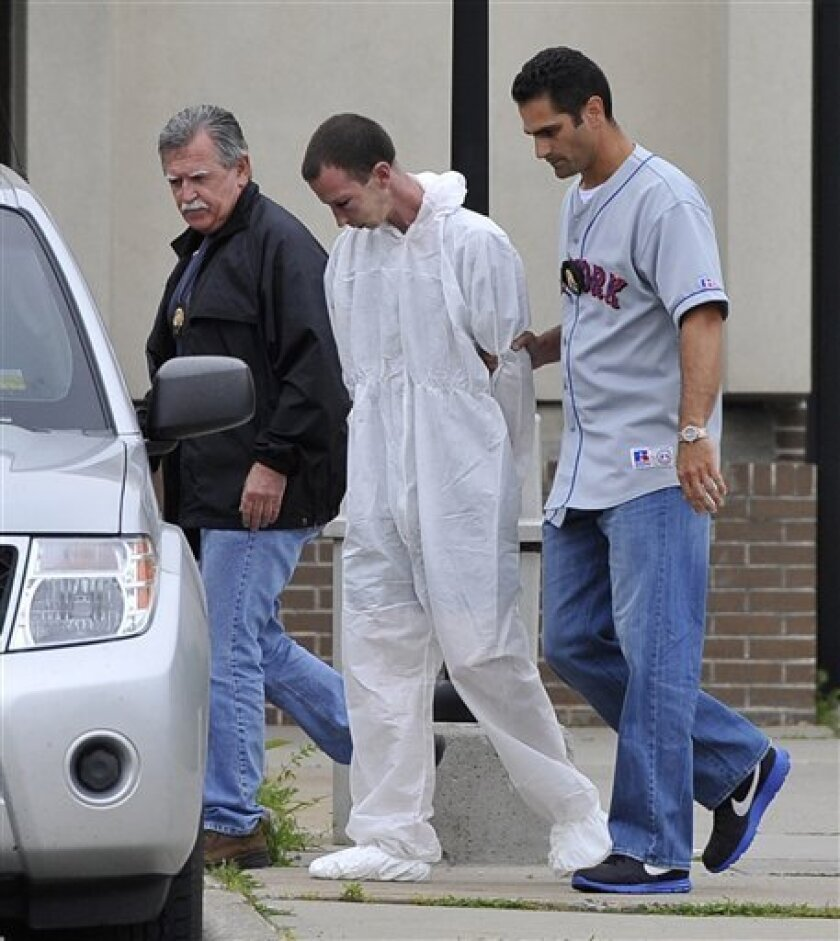 David Laffer, a suspect in the shooting deaths of four people at a pharmacy during a botched weekend painkiller robbery, is escorted out of Suffolk County Police Headquarters on Wednesday, June 22, 2011, in Yaphank, N.Y. (AP Photo/Kathy Kmonicek)