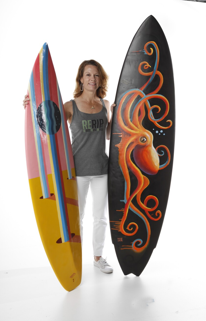 Meghan Dambacher and Lisa Randall run Rerip, a local nonprofit that repurposes surfboards. Here, she is seen with two surfboards painted by local artists that will be auctioned off at this year's ArtWalk in Little Italy.