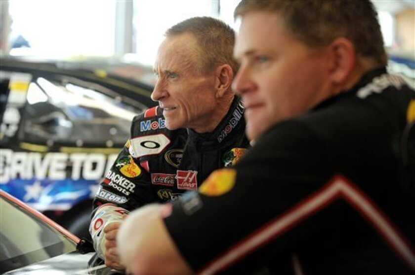 Driver Mark Martin, left, leans on his car in the garage area before practice for Sunday's NASCAR Sprint Cup Series auto race at Atlanta Motor Speedway, Saturday, Aug. 31, 2013 in Hampton, Ga. (AP Photo/David Tulis)