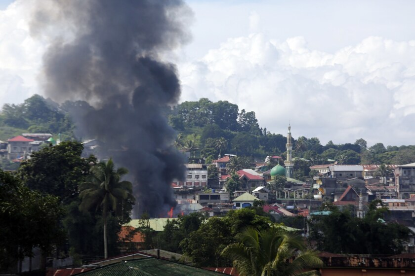 """Smoke rises from a fire after an airstrike inside the conflict area as fighting between Islamist militants and government forces continues in Marawi city on June 1, 2017. At least ten soldiers were killed in a """"friendly fire"""" incident during efforts to gain control of the city from militants allied with Islamic State."""