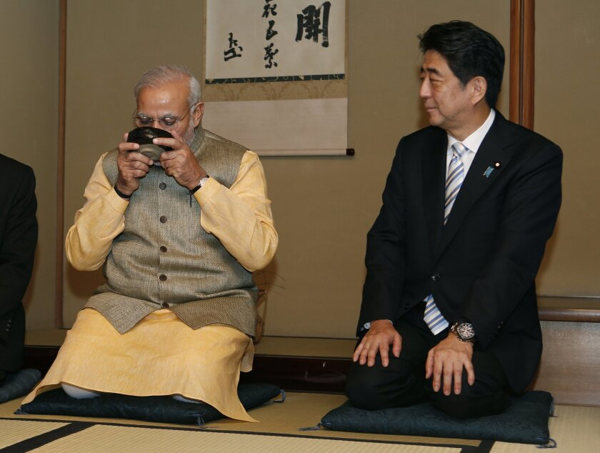 Japanese Prime Minister Shinzo Abe, right, watches Indian Prime Minister Narendra Modi drink a bowl of green tea during a tea ceremony at a tea hut of the Omotesenke, one of the main schools of Japanese tea ceremony, in Tokyo Monday, Sept. 1, 2014. Modi was on his official visit to Japan. (AP Photo/Yuya Shino, Pool)