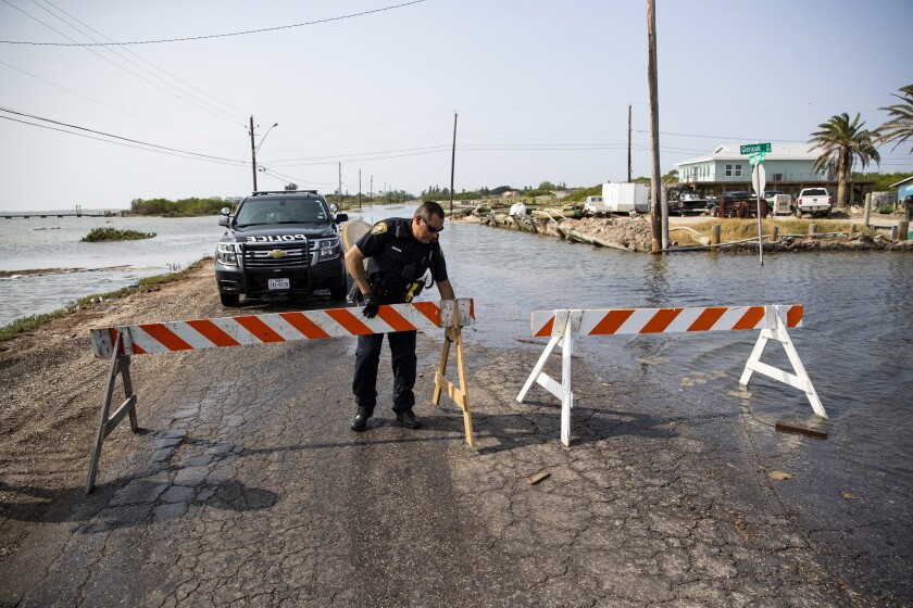 A police office places a barricade to close Laguna Shores Boulevard due to flooding on Sunday in Corpus Christi, Texas.