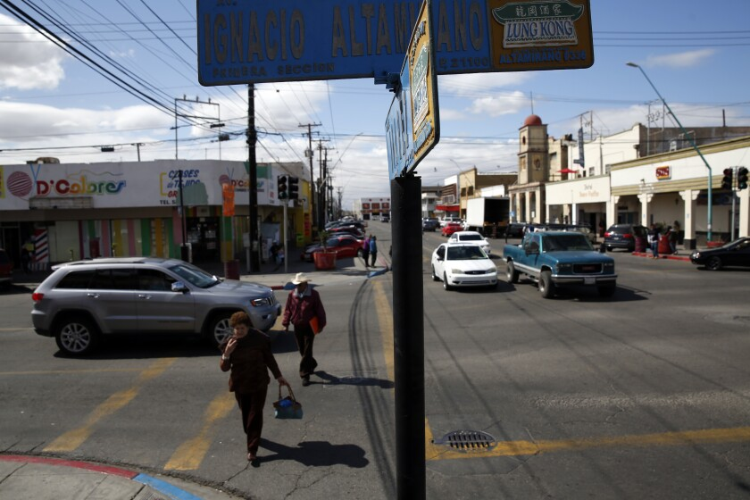 People cross the street under a street sign with both Spanish and Chinese characters in Mexicali, Mexico