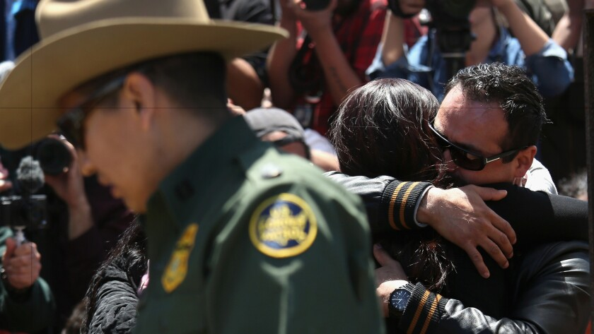 Under the supervision of the U.S. Border Patrol, families reunite at the fence separating San Diego and Tijuana in April.