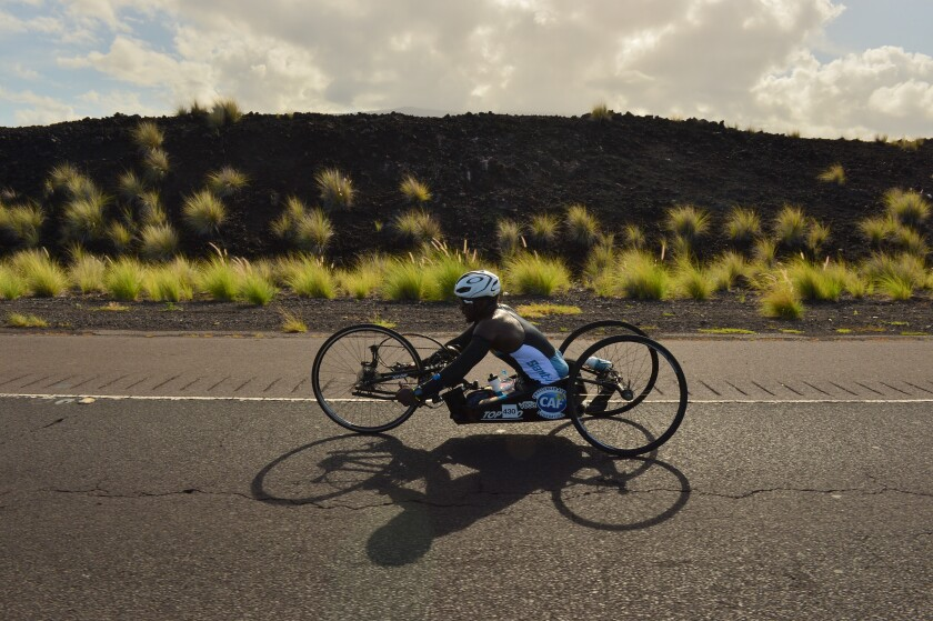 Roderick Sewell, 27, uses a kneeler-style handcycle to complete the 112-mile biking portion of the Ironman World Championship in Kailua-Kona , Hawaii, on Oct. 12.