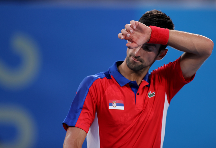 Novak Djokovic puts a sweatband-covered wrist to his forehead.