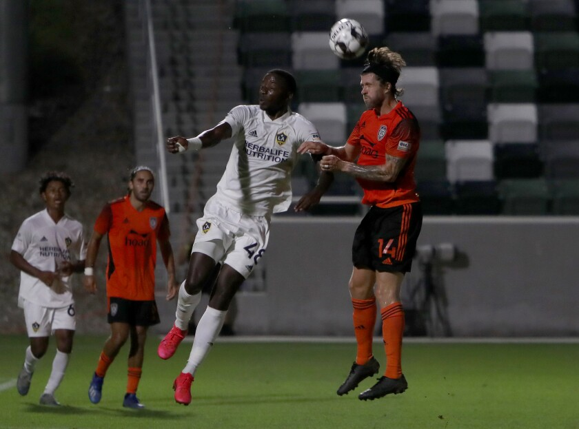 Orange County Soccer Club midfielder Aodhan Quinn, right, heads the ball against L.A. Galaxy II forward Augustine Williams.