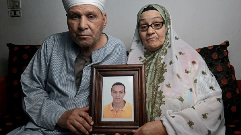 Abdel Shakour Abou Zeid and his wife hold a photo of their imprisoned son Mahmoud Abou Zeid, who is