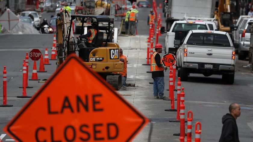 Construction crews conduct repairs on Broadway in San Francisco last year. Road construction firms are providing a major portion of the funds to defeat an initiative that would repeal an increase in state gas taxes.