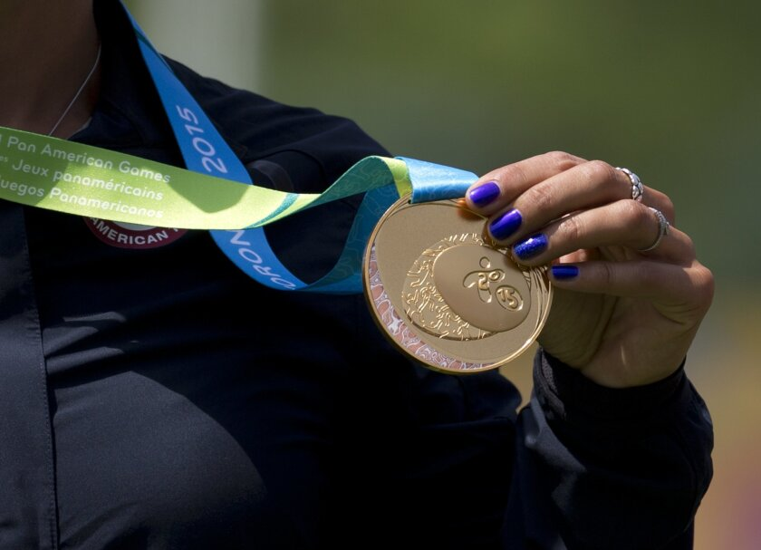 Khatuna Lorig of the U.S. holds up her gold medal for women's individual archery, during the medals ceremony, at the Pan Am Games in Toronto, Saturday, July 18, 2015.(AP Photo/Rebecca Blackwell)